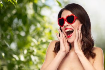 valentines day, beauty and people concept - happy smiling young woman with red lipstick and heart shaped sunglasses over green natural background. woman with red lipstick and heart shaped shades