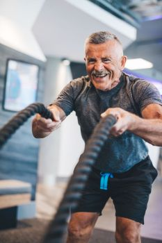 Senior man exercising with ropes at the gym. Physical activity and healthy lifestyle.. Senior man exercising with ropes at the gym.