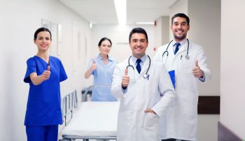 clinic, profession, people, health care and medicine concept - group of happy medics or doctors with gurney showing thumbs up at hospital corridor. happy doctors showing thumbs up at hospital