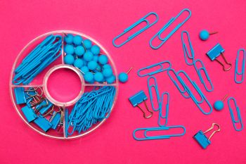 stationery paper clips, binders and buttons in blue on pink background