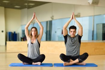 Young woman and man practicing yoga indoors. Two people doing exercises.