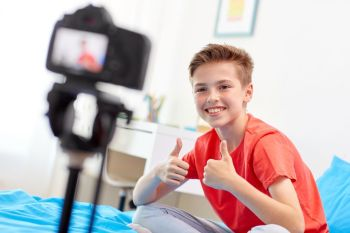 blogging, technology and people concept - happy smiling boy or blogger with camera recording video at home and showing thumbs up. happy boy with camera recording video at home