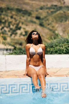 Relaxed woman sunbathing sitting on the edge of a swimming pool with sunglasses, tanned body, curly long hair, fashionable bikini. Relaxed woman sunbathing on the edge of a swimming pool
