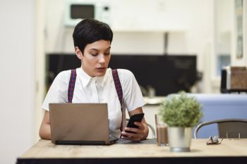 Young woman with very short haircut looking at her smart phone. Businesswoman working at home concept.