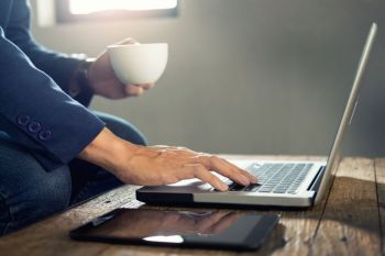 Close up of Business man hands busy working on his laptop and drinking hot coffee andsitting at wooden table in a coffee shop.