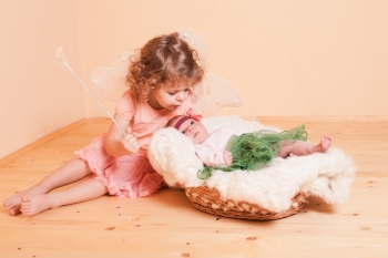 Little girl with her newborn sister in a basket