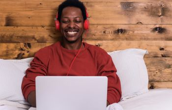 Young afro american man using his laptop with headphones in bed.