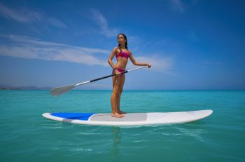 Girl standing on paddle surf board SUP in summer
