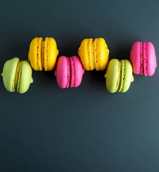 multi-colored round cakes with cream macarons on a black background, copy space