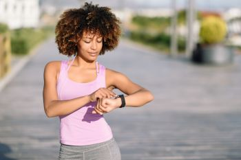 Young black woman using smartwatch touching touchscreen in active sports activity. Girl with afro hair looking at her smart watch screen.