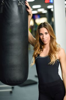 Female personal trainer with punching bag in a gym. Woman wearing sportswear clothes.