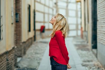 Happy young blond woman walking down the street. Smiling blonde girl with red shirt standing outdoors.