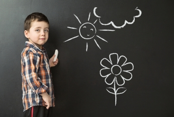 Little boy drawing on the blackboard