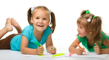 Two little girls draw with markers while laying on floor, isolated over white