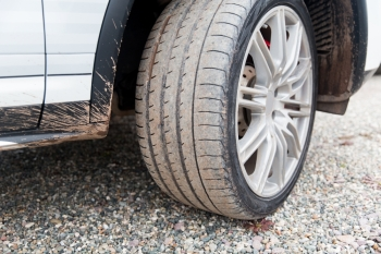 transport, driving and motor vehicle concept - close up of dirty car wheel on ground