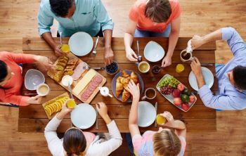 food, eating and family concept - group of people having breakfast and sitting at table. group of people having breakfast at table