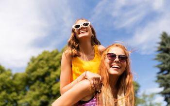 leisure, people and friendship concept - happy teenage girls or friends having fun at summer park. happy teenage girls having fun at summer park