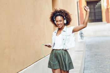 Young attractive black woman in urban street listening to the music with headphones and smartphone. Girl wearing casual clothes with afro hairstyle