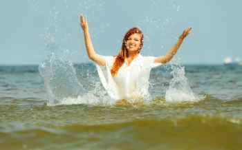 Vacation. Girl splashing water on the coast. Young woman having fun relaxing on the sea. Summertime.