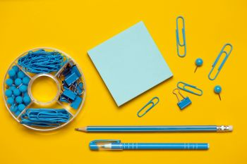stationery paper clips, binders, buttons, pencil, pen and paper in blue on yellow background