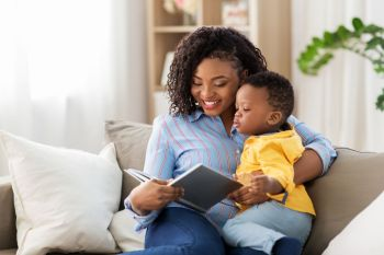 childhood, kids and people concept - happy african american mother with book and her baby son at home. african american mother with book and baby at home