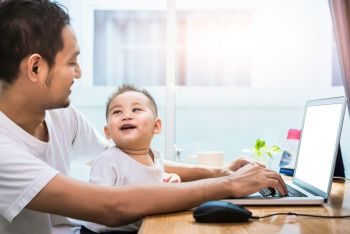 Single dad and son using laptop together happily. Technology and Lifestyles concept. Happy family and baby theme.