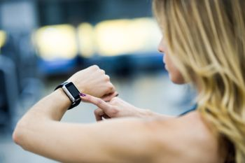 Young woman using smartwatch at the gym. Caucasian female working out.