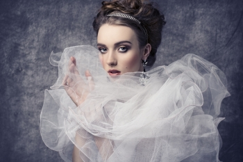fashion shoot of pretty woman with romantic retro dame style. Wearing baroque dress with frill veil collar, precious earrings and tiara in the hair-style, elegant make-up