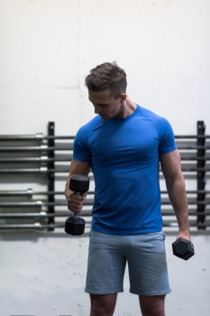 weight training fitness man inside working out arms lifting dumbbells doing biceps curls. Male sports model exercising indoors as part of healthy lifestyle.