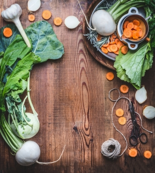 Vegetarian food background with fresh  organic local vegetables on wooden rustic kitchen table, top view, cooking preparation. Healthy food , vegan and clean diet eating concept