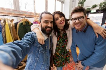 shopping, fashion and people concept - happy smiling friends taking selfie at vintage clothing store. friends taking selfie at vintage clothing store