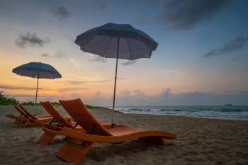 Orange beach chairs and parasols on sandy beach with morning sky and sea