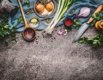 Cooking spoon with knife and cooking ingredients,  food background, top view, border
