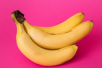 delicious ripe bananas on a pink background