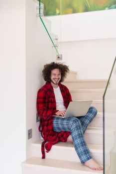 young freelancer in bathrobe working from home using laptop computer while sitting on stairs