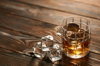 Glass of whiskey with ice cubes on rustic wooden table with copy-space