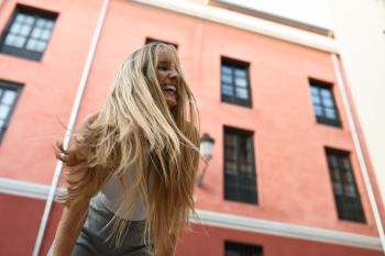 Happy young woman with moving hair in urban background. Blond girl, straight hairstyle, wearing casual clothes in the street.