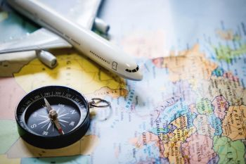 selective focus of miniature tourist on compass over map with plastic toy airplane,abstract background to travel concept.