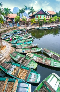 Vietnamese woman with conical hat Amazing morning view with Vietnamese boats at river. Tam Coc, Ninh Binh,. Vietnam travel landscape and destinations