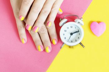 female hands with a bright pink-yellow gradient manicure on a yellow-pink background, a white alarm clock and a pink heart.
