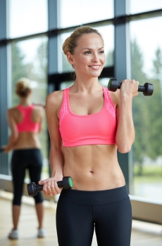 sport, fitness, training, weightlifting and people concept - young sporty woman with dumbbells flexing biceps in gym