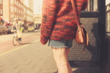 A young woman is waiting at the bus stop on a sunny day