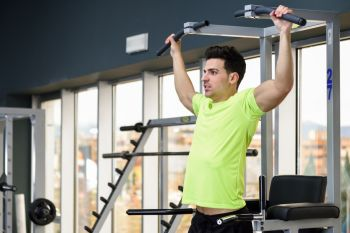 Young fit man wearing sportswear training at the gym. Healthy lifestyle and fitness concept.