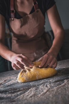 Woman Chef wearing apron kneading dough by hand at bakery