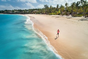 Aerial view of the running young woman on the white sandy beach near sea with waves at sunrise. Summer holiday. Top view of sporty slim girl, clear azure water. Indian Ocean. Lifestyle and sport