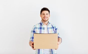 people and moving to new place concept - happy man holding cardboard box. happy man holding cardboard box