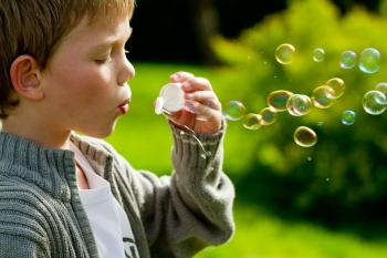 a little child blowing bubbles