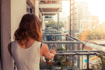 A young woman is relaxing on her balcony on a sunny day
