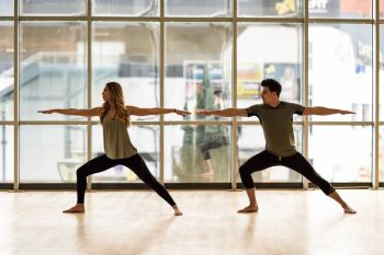 Young woman and man working out indoors. Two people doing exercises. Warrior 2 or Virabhadrasana II pose.