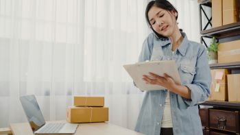 Smart Asian business woman owner of SME online using phone call receive from customer checking product on stock and write on clipboard working at home. Small business owner at home office concept.
